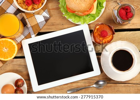 breakfast and tablet on wooden table - stock photo