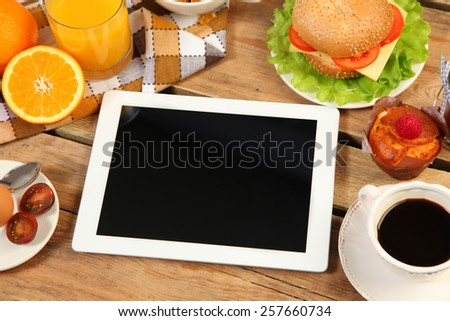 breakfast and tablet on wooden tablet - stock photo