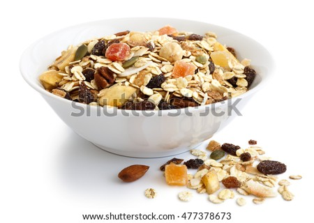 Breakfast bowl of fruit and nut muesli on white. Spilled muesli.