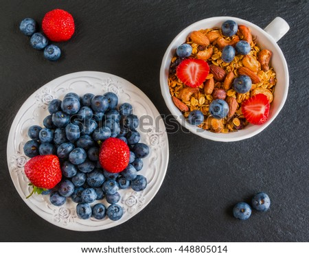 Breakfast bowl with granola made from oat flakes, dried fruits and nuts, and fresh blueberries and strawberries. Black stone background, top view. - stock photo
