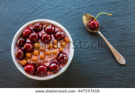 Breakfast bowl with yogurt,  granola or muesli or oat flakes, fresh cherries and nuts. Black stone background, top view. - stock photo