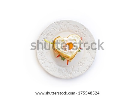 Breakfast, bread with a heart of fried egg and vegetables - stock photo