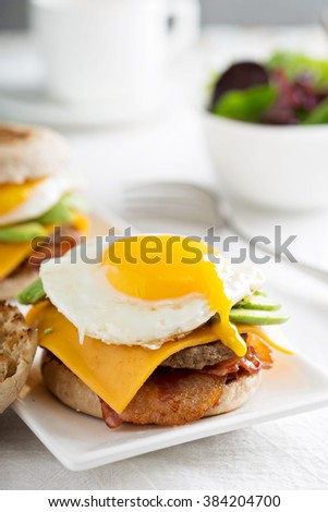 Breakfast burger with fried egg and avocado, cheese and bacon