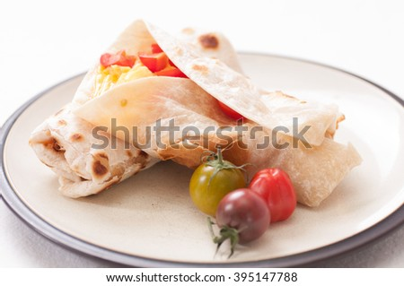 breakfast burrito with cheese, eggs and heirloom cherry tomato