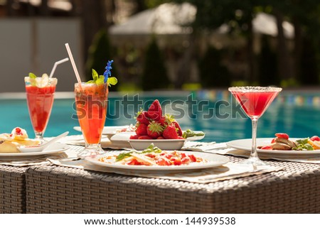 Breakfast by the pool. Light snacks, fresh strawberries, fruit smoothies. - stock photo