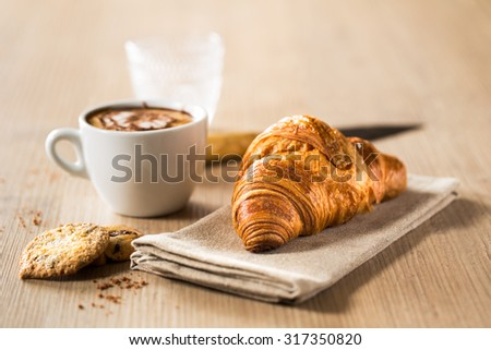 Breakfast capuccino, croissant and delicious cookies on a wooden table. - stock photo