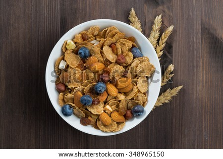 breakfast cereal flakes with blueberries and nuts on a dark wooden table, top view, horizontal - stock photo