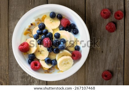 Breakfast cereal with blueberries, bananas and raspberries on a rustic wood background, overhead view - stock photo