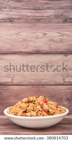 Breakfast cereal with dried raspberry fruit pieces in white bowl over wooden background