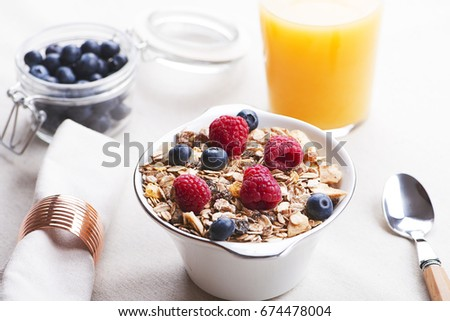 Breakfast cereal with raspberries and blueberries next to orange juice.