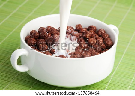 Breakfast cereals, chocolate balls with milk - stock photo