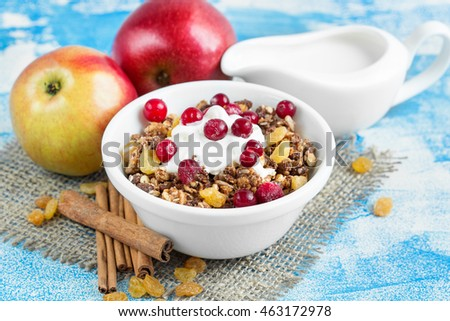 breakfast cereals, fresh apples and cinnamon, dried fruit and cream on a light background