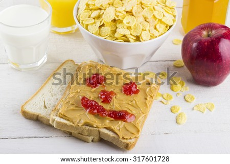 Breakfast: cereals, milk, orange juice, sandwich with peanut butter and jam on a white wooden background