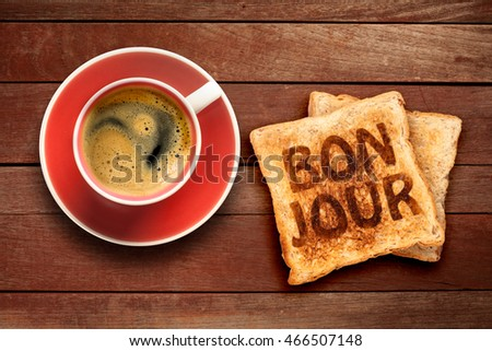 Breakfast, coffee and toast with a text bonjour, on a wood background