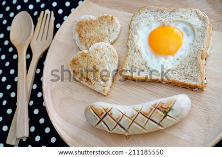Breakfast consist of toast with fried egg in shape of heart and big sausage. Concept about love and relationship.                               - stock photo