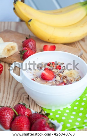 breakfast consisting of vanilla greek yogurt topped with granola, sliced bananas and strawberries, on an old wooden textured table with green fabric