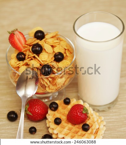 Breakfast - cornflakes with glass of milk. Wafes, black currants and strawberries. - stock photo