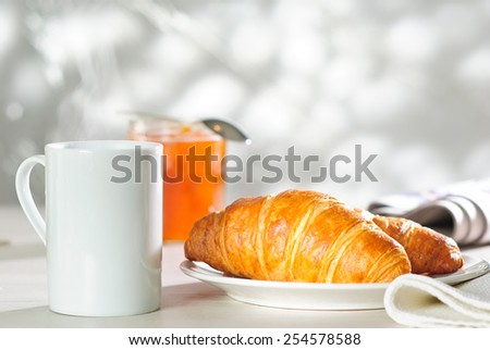 breakfast croissant, apricot jam and cup of hot drink