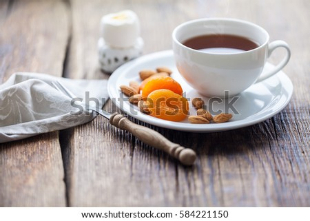 Breakfast. cup of tea with dried apricots, almonds and soft-boiled egg