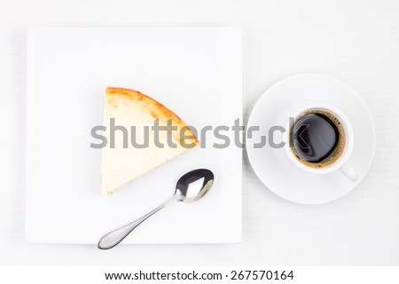 Breakfast eating background. Cup of coffee with piece of cheesecake on plate. Cup of espresso with dessert on white table - stock photo