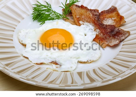 Breakfast - egg with roasted bacon and dill - stock photo