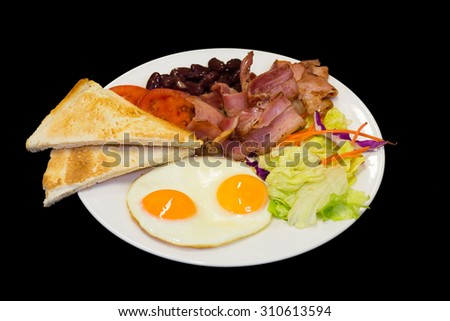Breakfast Eggs, bacon, toast, salad and tomato. All on black background - stock photo