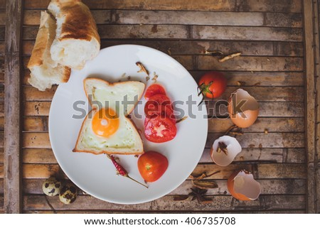 Breakfast foods toast , egg, tomato , bread  on white plate on brown background desk rustic style