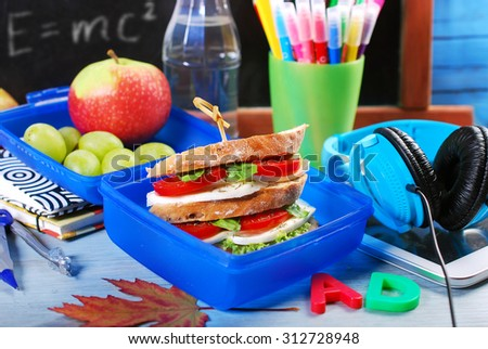 breakfast for school with layered caprese sandwich in blue lunch box - stock photo