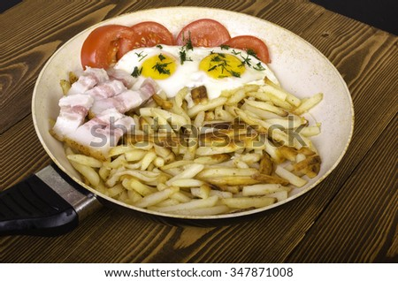 Breakfast for two. Frying pan with two fried eggs and fried potatoes. On wooden background. - stock photo