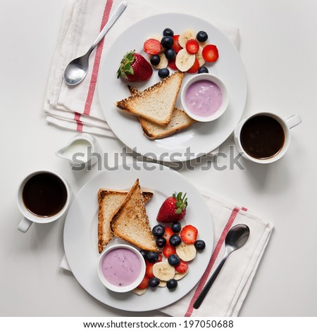 Breakfast for two with toast, coffee and berries