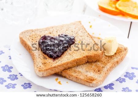 Breakfast for valentines day with toast, jam and orange - stock photo
