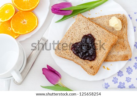Breakfast for valentines day with toast, jam, orange and tulips - stock photo