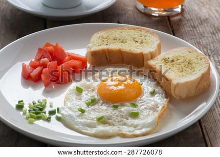 Breakfast fried egg with garlic bread - stock photo