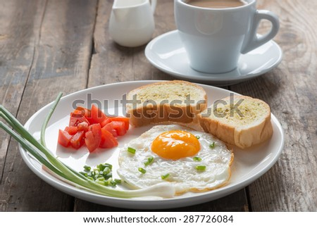 Breakfast fried egg with garlic bread, a cup coffee - stock photo