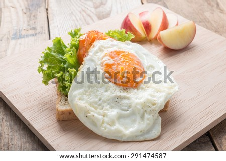Breakfast fried egg with tomato and lettuce on wood board