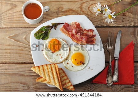 Breakfast - fried eggs, toast, bacon and tea and chamomile on wooden background. the view from the top - stock photo