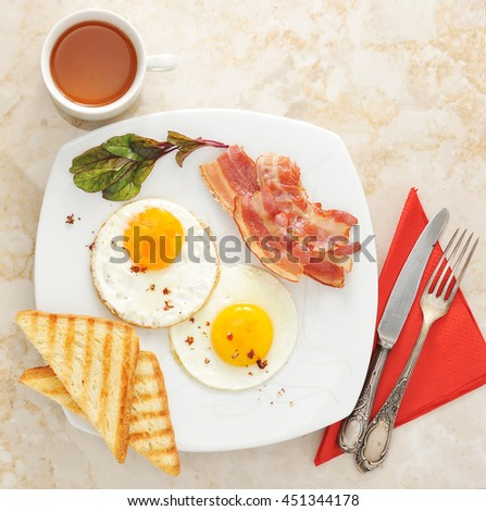 Breakfast - fried eggs, toast, bacon and tea on marble background. the view from the top - stock photo