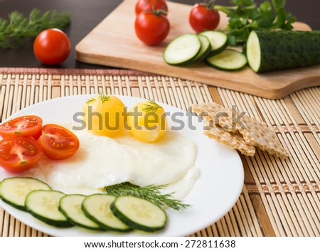 Breakfast. Fried Eggs (with a raw egg yolk) and Vegetables - stock photo