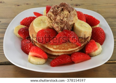 Breakfast from Pancakes garnished with cut Strawberries and Bananas and with Ice Cream with added Maple Syrup served in white porcelain dish over wooden table