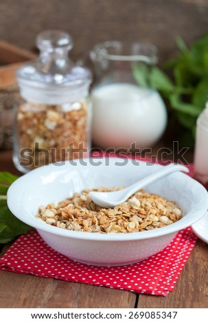 Breakfast: homemade granola in a white plate, yogurt with jam and a jug of milk on a wooden table. Selective focus.