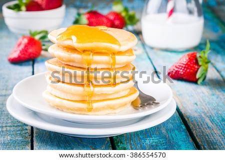 Breakfast: homemade pancakes with honey and strawberries - stock photo