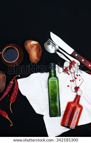 Breakfast,  hot coffee, potatoes, red dry peppers, food background, on back background. Top view . Silver fork and spoon. Food. Breakfast time. Eating. Potatoes, garlic. Green and brown glass bottles - stock photo