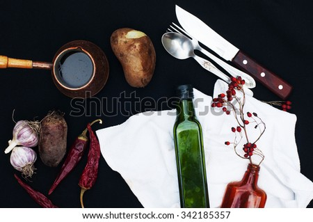Breakfast,  hot coffee, potatoes, red dry peppers, food background, on back background. Top view . Silver fork and spoon. Food. Breakfast time. Eating. Potatoes, garlic. Green and brown glass bottles