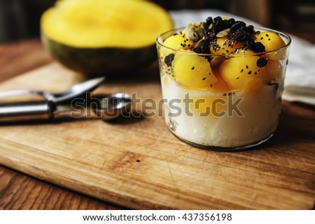 Breakfast idea; fresh mango scoops with almonds yogurt topped with mixed sunflower seeds, chia seeds, and dried raisins.  - stock photo