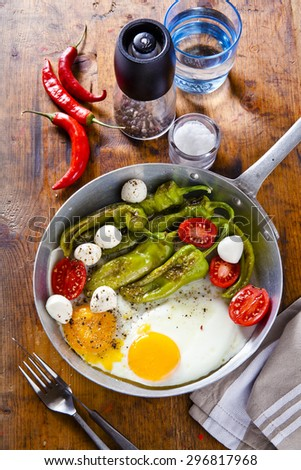 Breakfast in a frying pan. fried eggs with salad. fried green peppers, tomatoes, fresh mozzarella cheese. on a wooden table. background for restaurants. fork and knife. pepper and salt. - stock photo