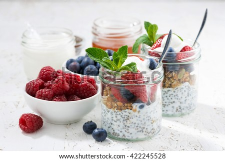 Breakfast in a jar with chia, berries and oat flakes on white background, closeup, horizontal - stock photo