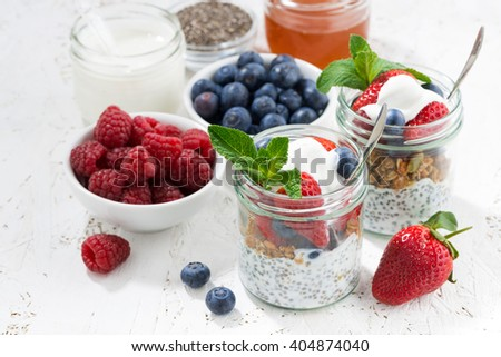 Breakfast in a jar with chia, berries and oat flakes, top view, horizontal