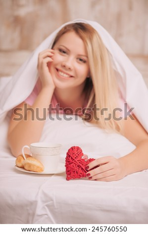 Breakfast in bed. Closeup image of young woman covered with blanket having french breakfast with coffee and croissants served to bed due to valentines day, selective focus on rustic gift hearts - stock photo