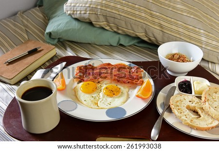 Breakfast in bed/Traditional breakfast of fried eggs & bacon with coffee, bagel and oatmeal in bowl on wood serving tray on unmade bed - stock photo