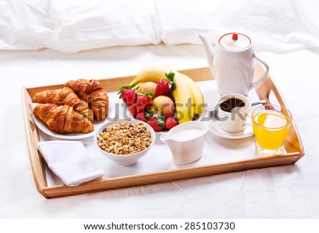 breakfast in bed. Tray with coffee, croissants, cereals and fruits - stock photo